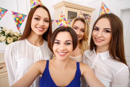 appealing: Party selfie. Four appealing young girls are looking into the camera to make party selfie.