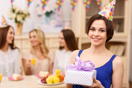 happy moment: Happy moment. Attractive young girl is smiling brightly while holding her birthday present