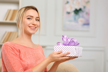 upholding: Pleasant surprise. Young pleasing woman is smiling while upholding wrapped gift box. Stock Photo
