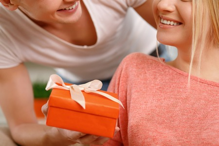 happy moment: Happy moment. Boyfriend is giving small present box to his girlfriend.