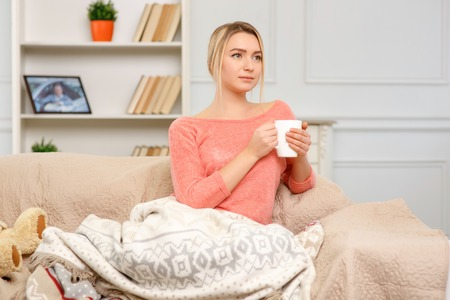 pleasing: Comfy at home. Young pleasing woman sitting on the sofa and drinking tea.