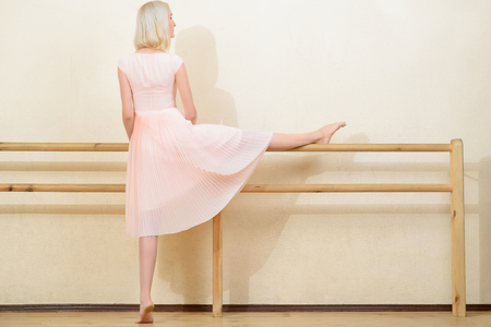 ballet bar: Stretching procedure. Slender young woman stands beside the wall and stretches while leaning on ballet bar. Stock Photo