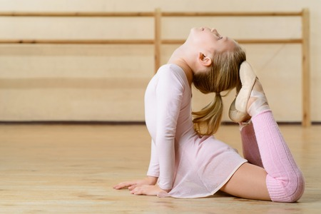 thorough: Thorough stretching. Little girl is lying on the floor and doing stretching exercises