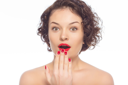 appealing: Surprised expression. Young appealing lady holds hand at her mouth looking surprised. Stock Photo