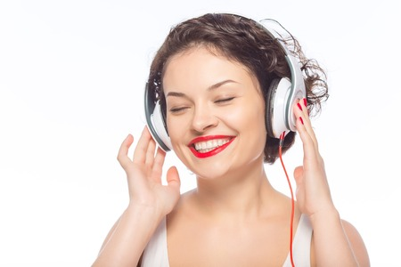appealing: Enjoying the music. Young appealing woman is smiling brightly while wearing headphones.