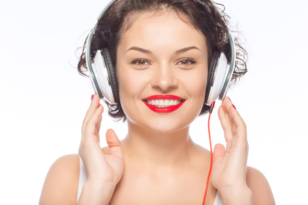 appealing: Posing with headphones. Young appealing woman is smiling brightly while wearing headphones. Stock Photo