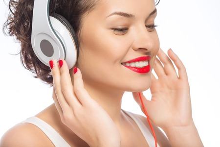 appealing: Posing with headphones. Young appealing woman wearing big headphones. Stock Photo