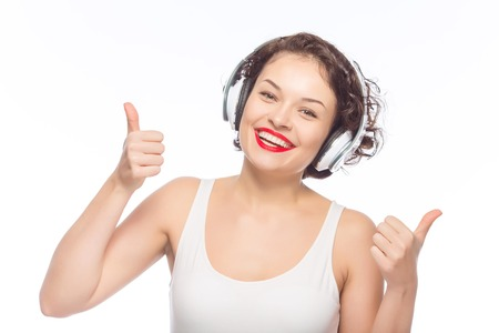 feeling up: Positive moments. Young smiling attractive woman in headphones is showing thumbs up. Stock Photo