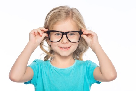 Girl in glasses. Little girl is smiling while trying glasses on.