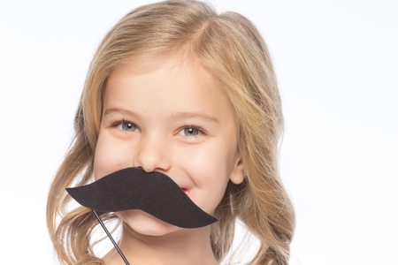 upholding: Girl with paper moustache. Little girl is smiling while upholding decorative paper moustache. Stock Photo