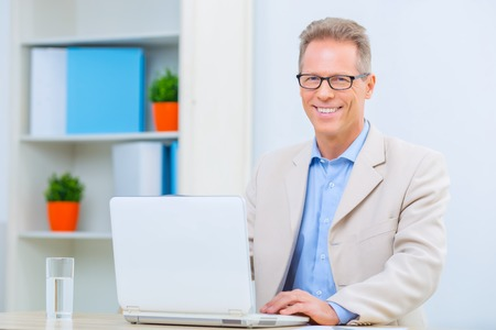 Positive attitude. Handsome businessman is sitting at his desk and smiling brightly.