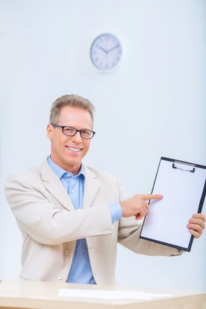 upholding: Successful results. Smiling businessman is upholding his clipboard and showing some records.