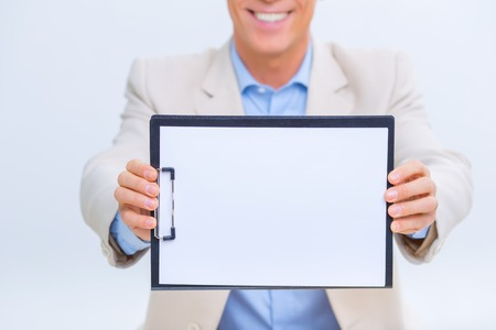 upholding: Successful results. Smiling businessman is upholding his clipboard and showing records.