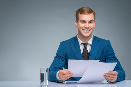 newsman: Attractive broadcaster. Handsome newsman is smiling while holding papers for broadcasting.
