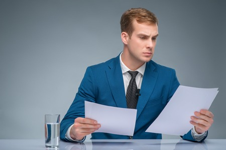 newsman: Absorbed in news. Handsome newsman looks occupied with reading important files. Stock Photo