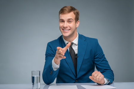 newsreader: Attractive broadcaster. Handsome newsman is smiling while leading the newscast. Stock Photo