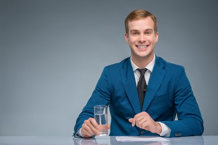 commentator: Attractive broadcaster. Handsome newsman is smiling while holding a glass of water. Stock Photo