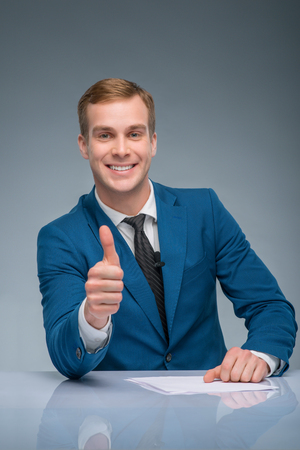 newsman: Positive man. Handsome newsman is smiling and showing thumbs up.