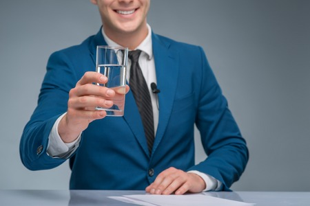 upholding: Confident man. Smiling handsome newsman is upholding a glass of water.