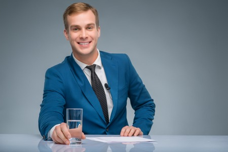 newsman: Confident man. Smiling handsome newsman is holding a glass of water.