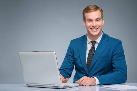 newsman: Digital information. Handsome smiling newsman working with his laptop.