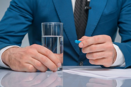newsman: Taking a pill. Handsome newsman holding glass of water and a pill.