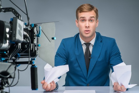newsman: Clutching papers. Handsome newsman looks tremendously stressed and confused while clutching papers. Stock Photo