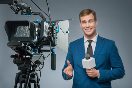 reportero: reportero sonriendo. Apuesto presentador sonriendo defensa de su micrófono y dirigir las noticias.
