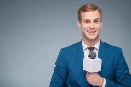 reportero: reportero sonriendo. Apuesto presentador sonriendo defensa de su micrófono.