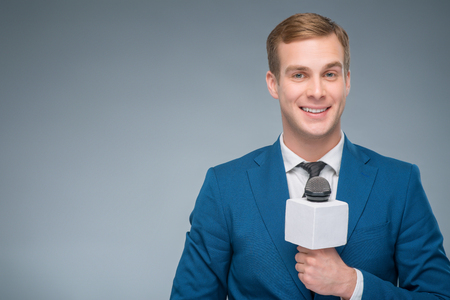 upholding: Smiling reporter. Handsome smiling newscaster upholding his microphone.