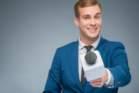 newsman: Asking questions. Smiling handsome newscaster in the process of taking an interview. Stock Photo
