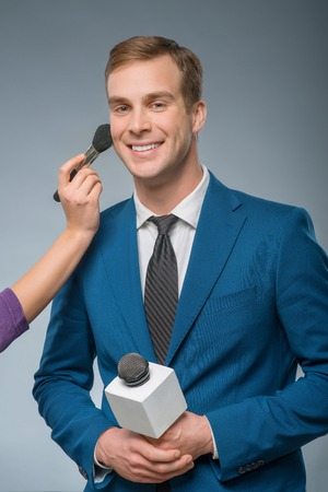 'getting ready': Getting ready. Handsome male reporter is smiling while getting ready for the broadcast