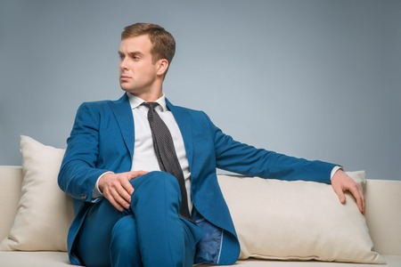 supervisory: Attractive businessman. Handsome young businessman looks serious while sitting on the sofa. Stock Photo