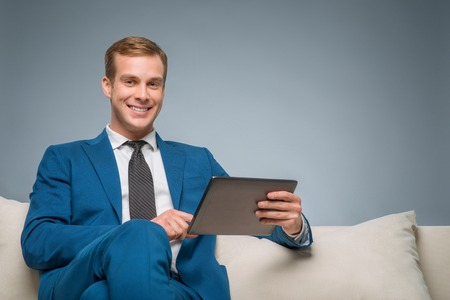 supervisory: Busy with gadget. Smiling handsome businessman is sitting on the sofa and holding his digital tablet.