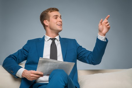 upholding: Calling somebody up. Appealing businessman is sitting with newspaper and upholding his hand to call somebody.