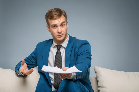 upholding: Businessman with papers. Handsome young businessperson is sitting on the sofa upholding papers. Stock Photo