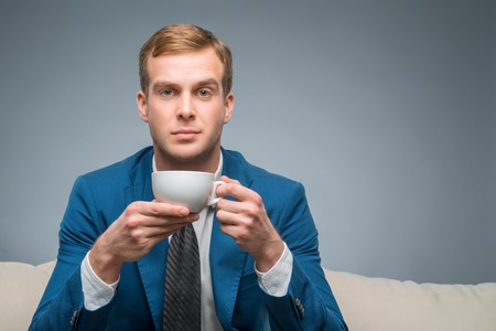 upholding: Tea time. Handsome young businessman is sitting on the sofa and upholding a cup of tea.