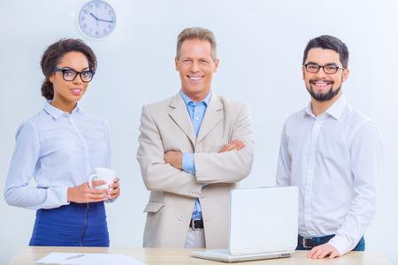 beau mec: Les gens prosp�res. Trois employ�s de bureau sont souriants agr�ablement tout en posant sur la cam�ra.
