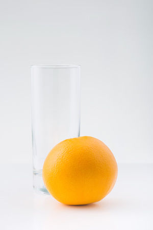 two objects: Two objects. Picture of an orange and empty transparent glass on white surface.