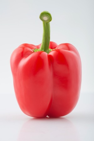 pecks: Bulgarian pepper. Big ripe red Bulgarian pepper is lying on the surface.