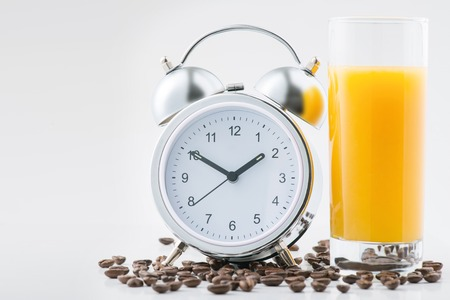 vibe: Morning vibe. Alarm clock and a glass of fresh morning orange juice are standing on the surface covered with coffee beans