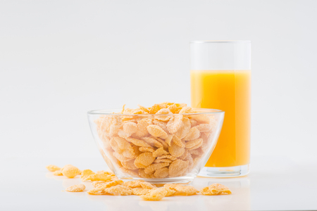 cornflakes: Light breakfast. Glass of orange juice and bowlful of cornflakes are standing on white surface. Stock Photo
