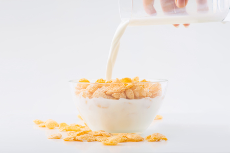 lactic: Breakfast dish. Glass of milk is being poured into bowlful of corn flakes.