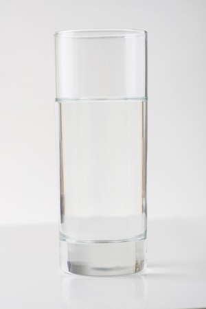 still water: Clear water. Transparent glassful of still water is standing on white surface. Stock Photo