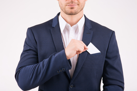 Business card. Businessman taking out his business card from breast pocket. Stock Photo