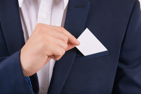 Card for advertising. Male hand taking out business card from breast pocket.