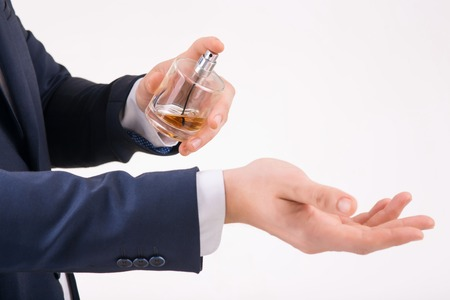eau de perfume: Perfume aroma. Person holding perfume with one hand and spraying it on his wrist.