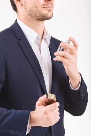 eau de perfume: Using the perfume. Man standing and spraying perfume over himself.