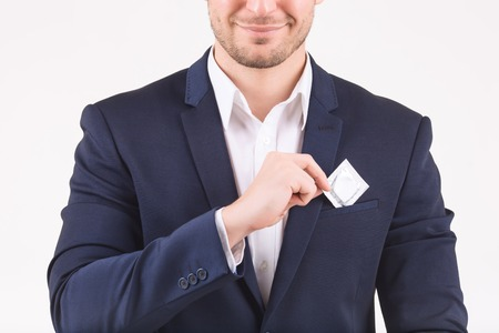 breast pocket: Safety measures. Smiling man putting condom into his breast pocket. Stock Photo