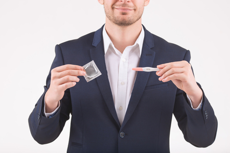 upholding: Opposing things. Smiling man upholding a condom and pregnancy test in different hands.